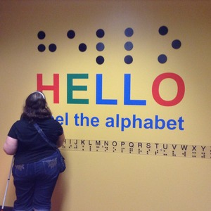 """Bookshare member Amber Steet readsthe Braille alphabetand """"Hello"""" greeting in Braille on display at San Antonio Central Library."""
